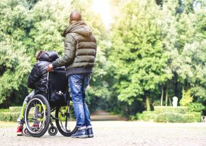 An adult male pushes a wheelchair holding another person outside surrounded by trees near a park