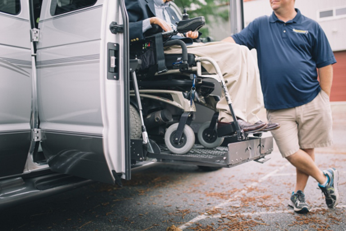 Platform Lift Systems -- Example showing a powerchair being lowered from the side of a vehicle