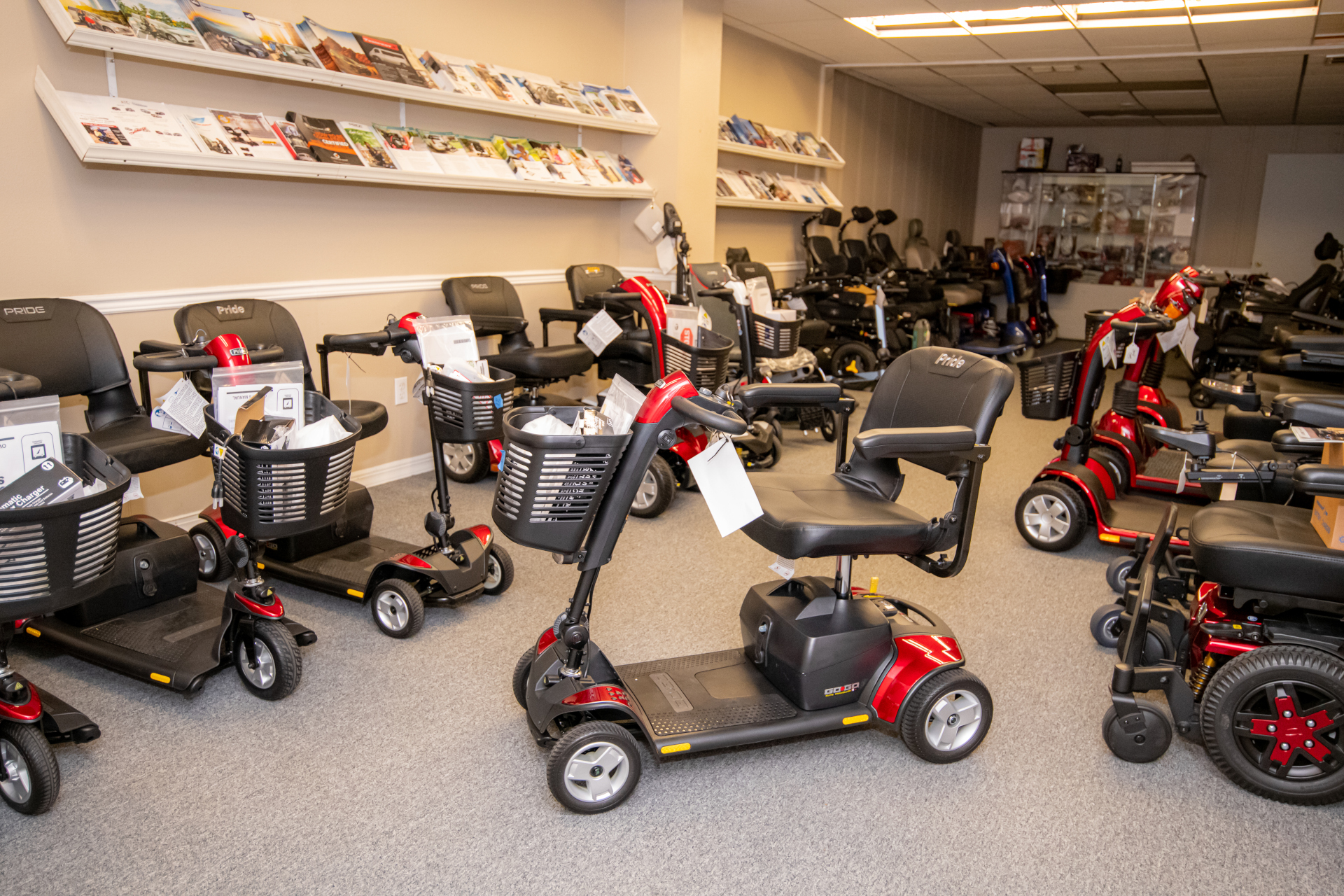 Mobility Scooters: A display floor filled with various designs and types of mobility scooters and power chairs